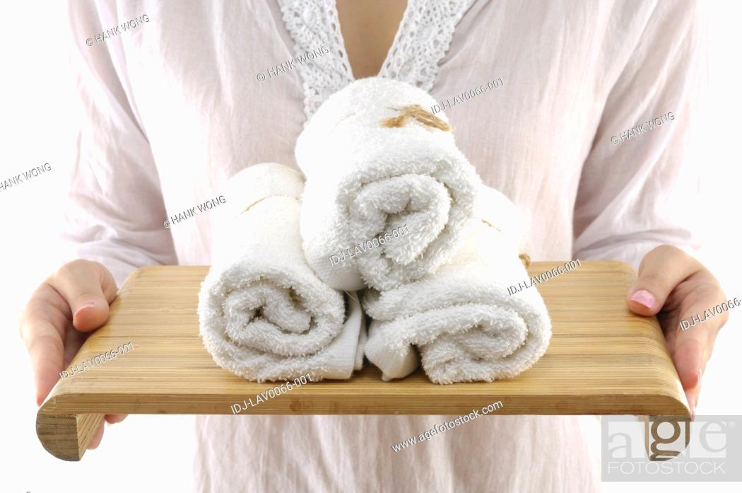 Stock Photo: Woman holding towels in a tray.