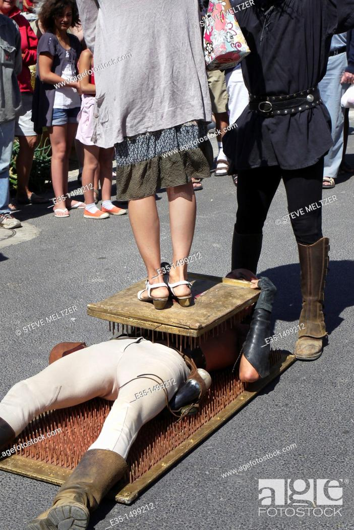 Stock Photo: A performer at the wine festival in Fontes, France, entertains the crown by laying on a bed of nails as a woman stands on him during a street show.