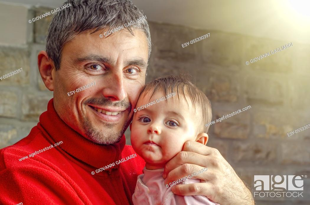 Photo de stock: Happy father holding his daughter at home. Family concept.