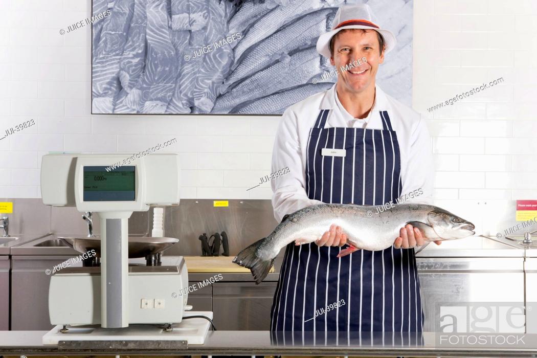 Photo de stock: Fishmonger In Fresh Fish Department Of Supermarket.