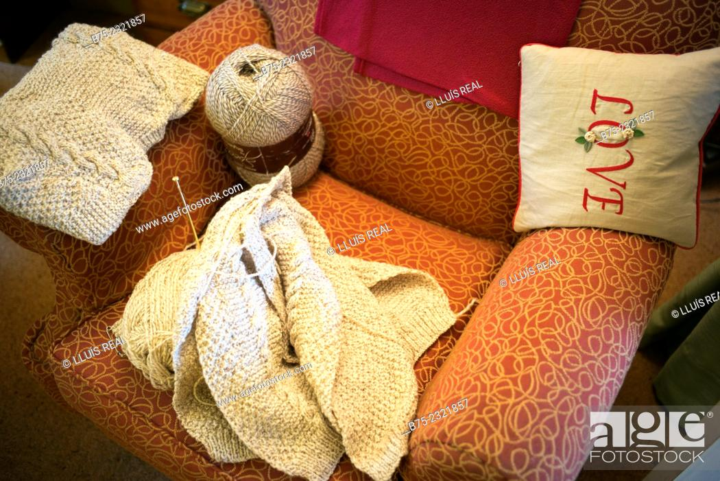 Stock Photo: Knitting handmade with a ball of wool on a chair with a small cushion hand embroidered with the word LOVE.