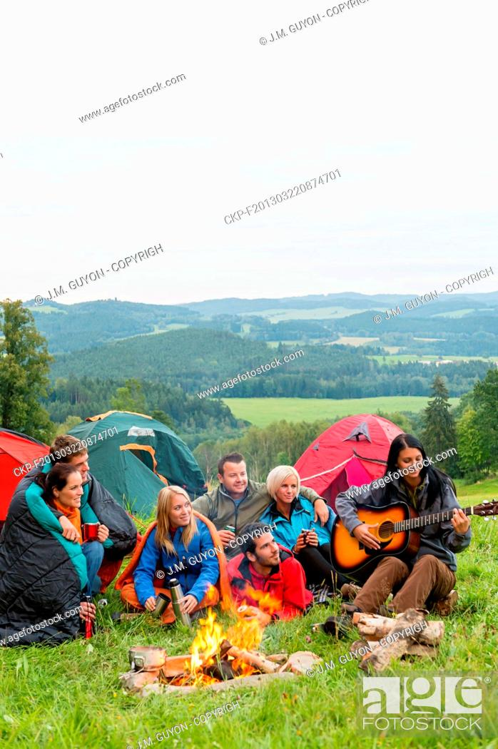 Imagen: Group of friends sitting beside tents, campfire girl playing guitar.