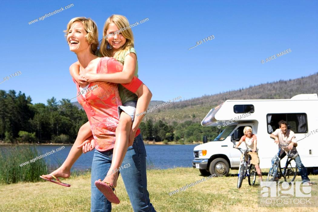 Stock Photo: Girl 9-11 on mother's back, father and brother 10-12 by motor home in background.