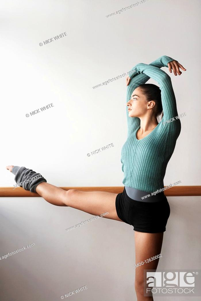 Stock Photo: Ballet Dancer Stretching at bar.