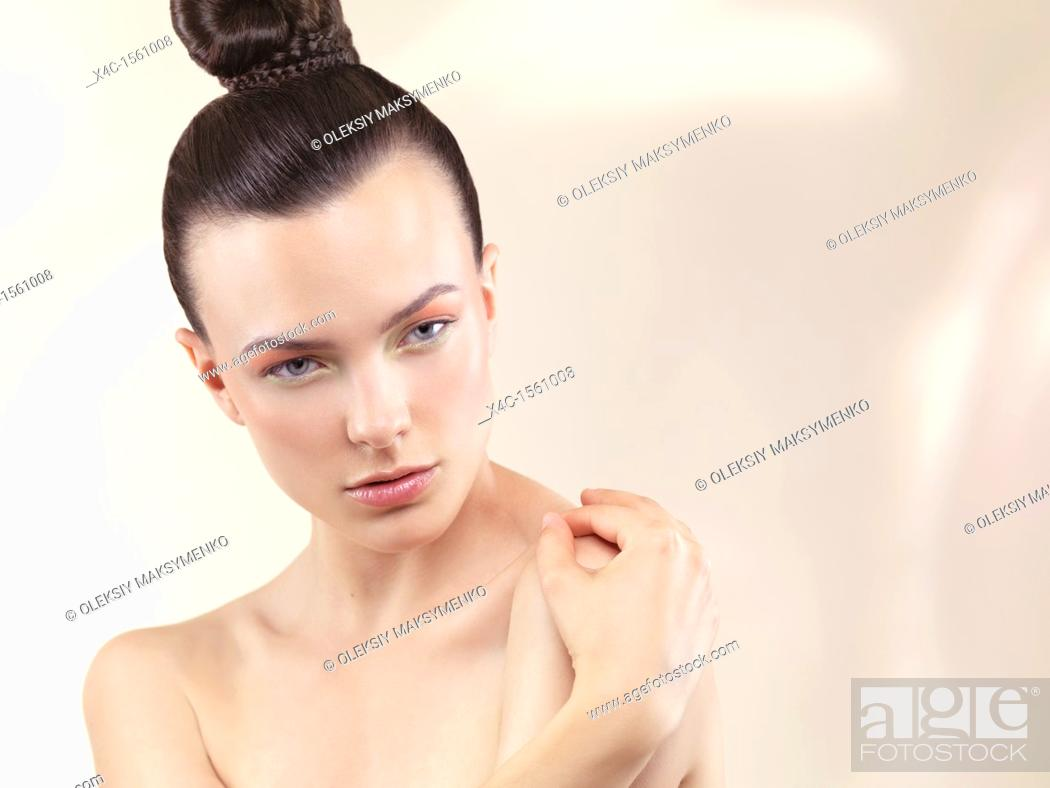 Stock Photo: Beauty portrait of a young woman with wearing soft pastel color makeup and top knot hairstyle.