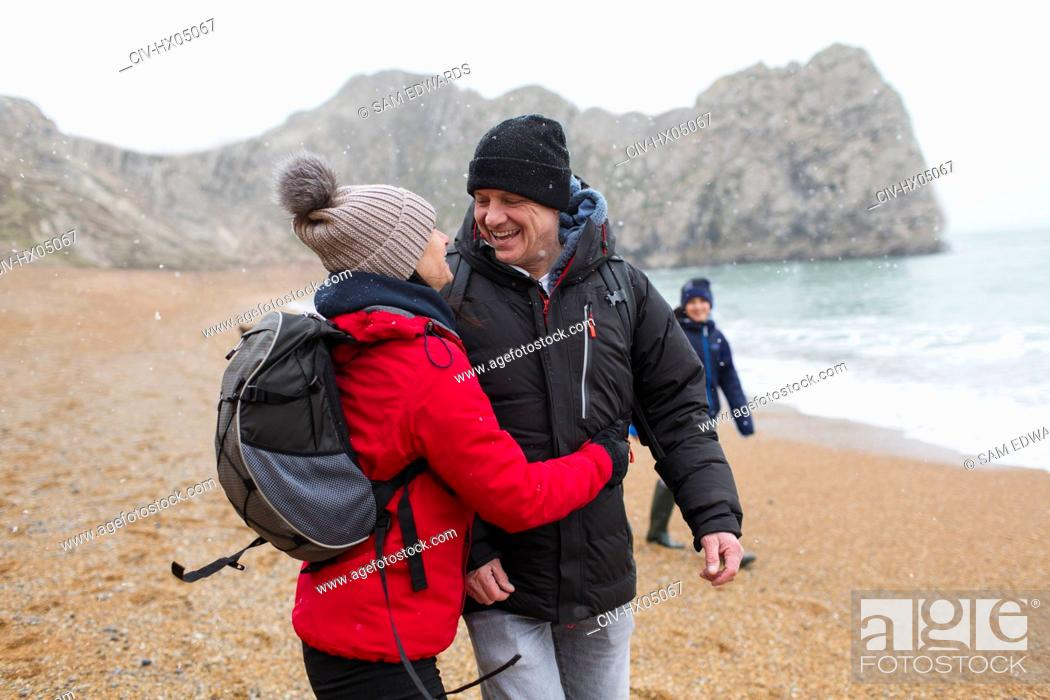Stock Photo: Affectionate, happy couple in warm clothing on snowy winter beach.