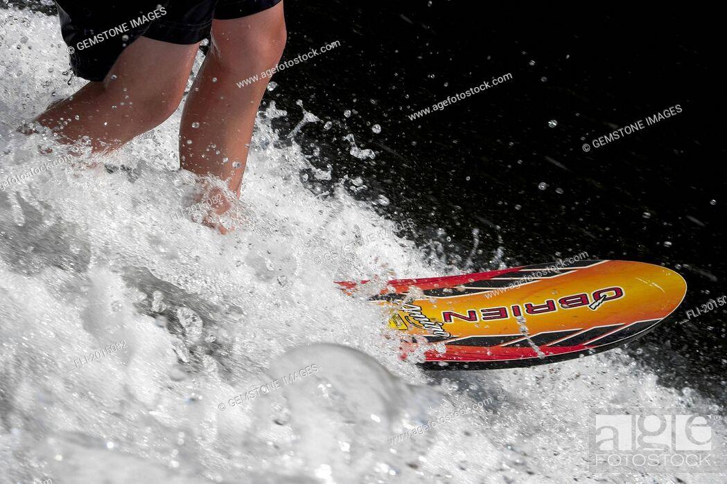 Stock Photo: Boy's Legs On Water Ski.
