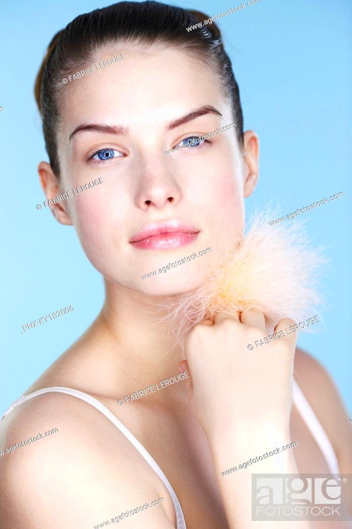 Stock Photo: Young woman holding powder puff.