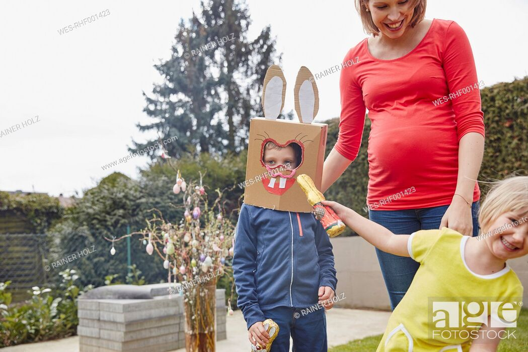 Stock Photo: Pregnant mother with boy wearing bunny mask and happy girl in garden.