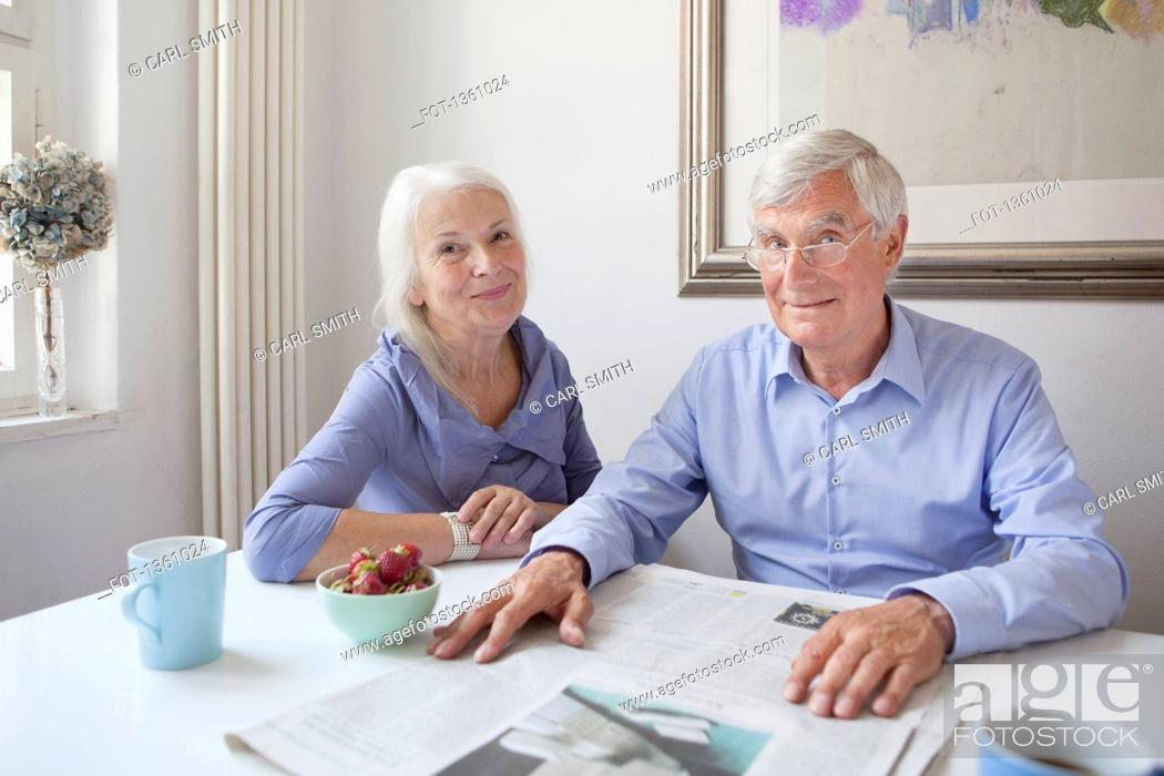 Stock Photo: Portrait of happy senior couple sitting with newspaper at table.
