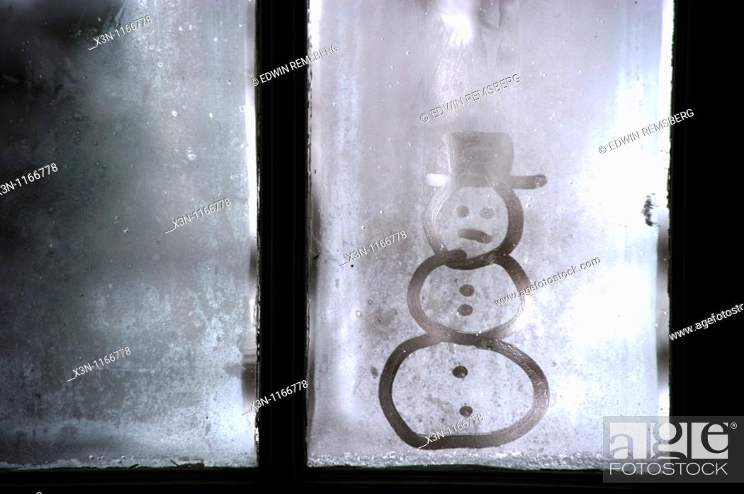 Stock Photo: Snowman image on frosty window.