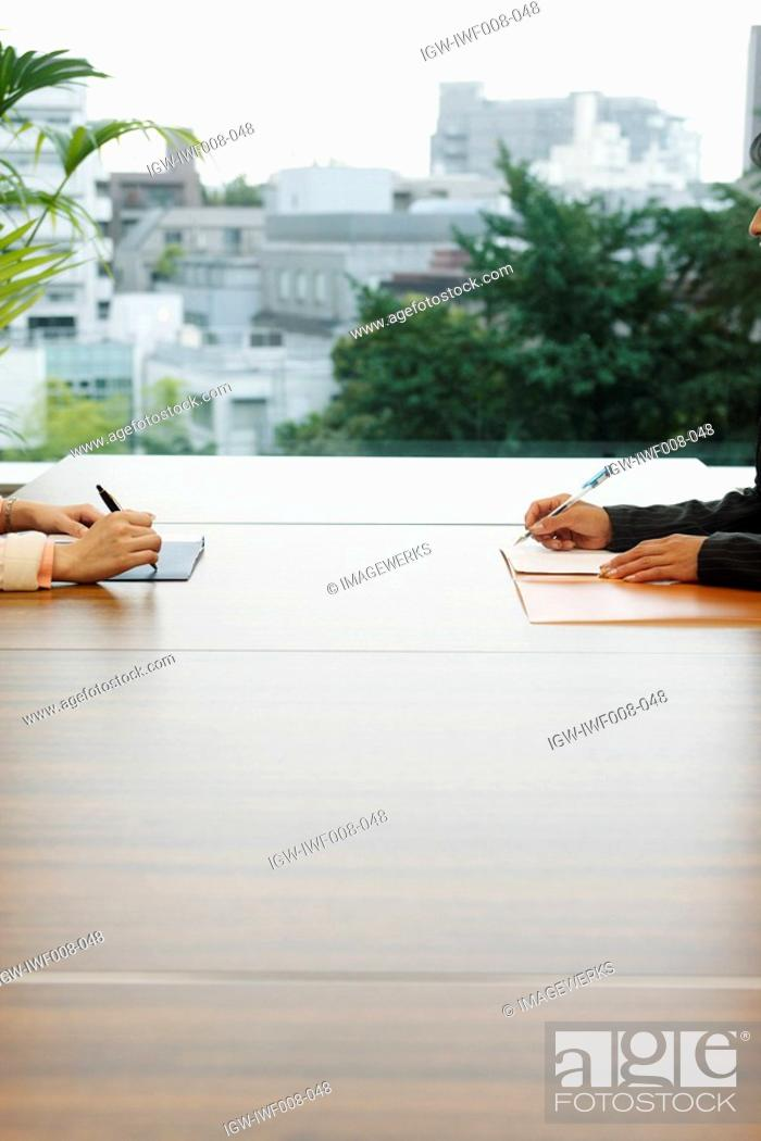 Stock Photo: Two people working together on a large wooden table placed in the terrace.