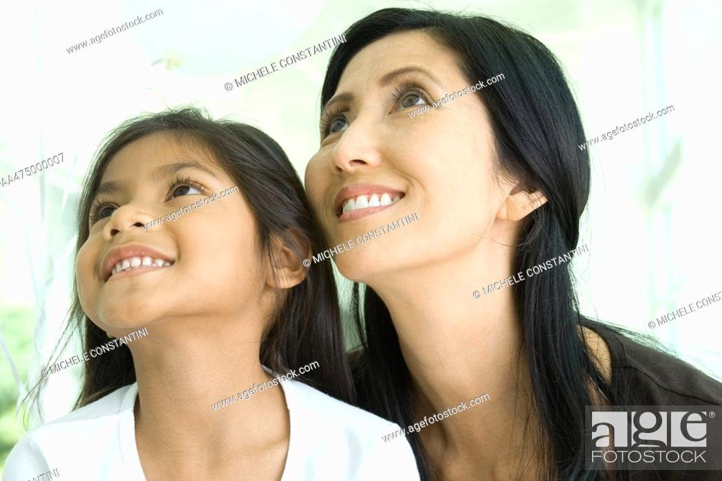 Stock Photo: Mother and daughter looking up and smiling together, close-up.