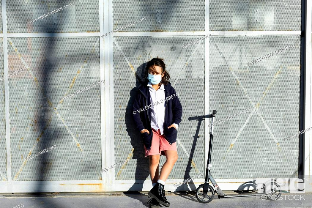 Photo de stock: Portrait of boy wearing protective mask with scooter in the city.