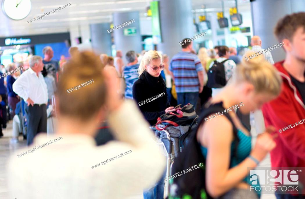 Photo de stock: Casual blond young woman using her cell phone while queuing for flight check-in and baggage drop. Wireless network hotspot enabling people to access internet.