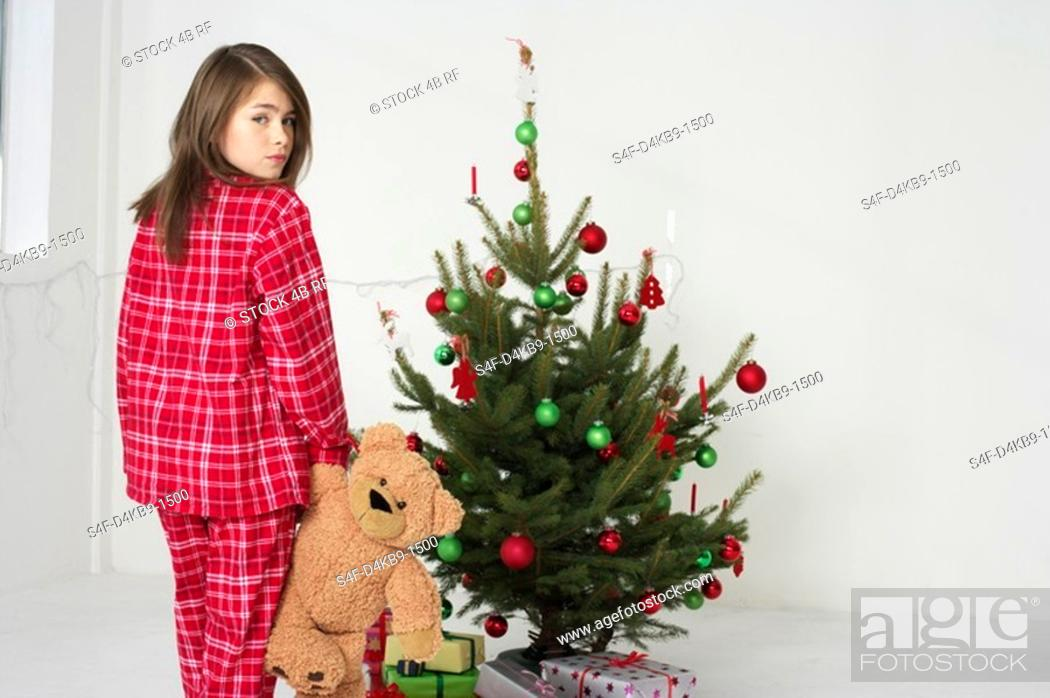 Stock Photo: Girl wearing pajamas sneaking off to Christmas tree.