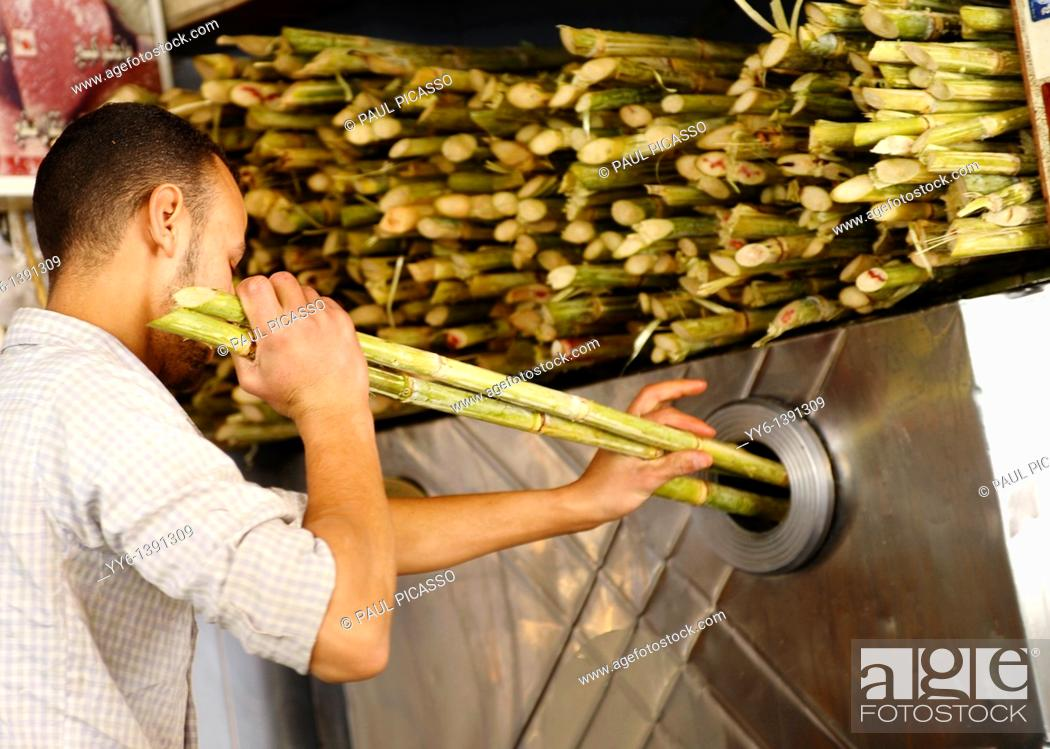 Stock Photo: sugar cane being pressed to make fresh juice , Souq al Gomaa Friday Market in Cairo , Egypt.