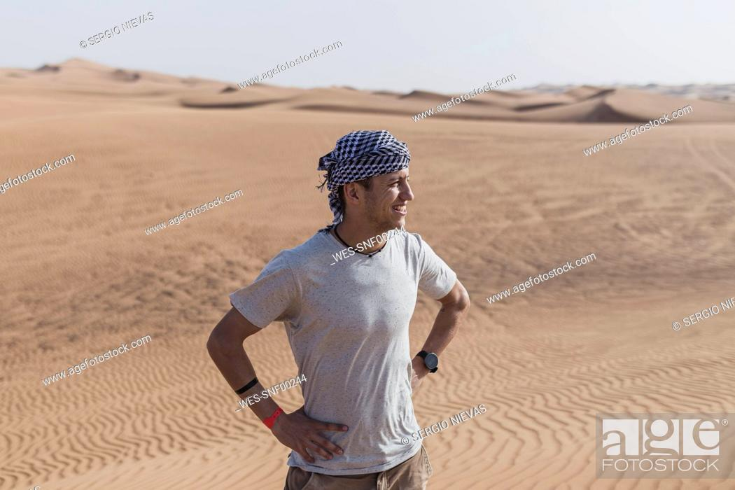 Stock Photo: Male tourist looking away while standing on sand dunes in desert at Dubai, United Arab Emirates.