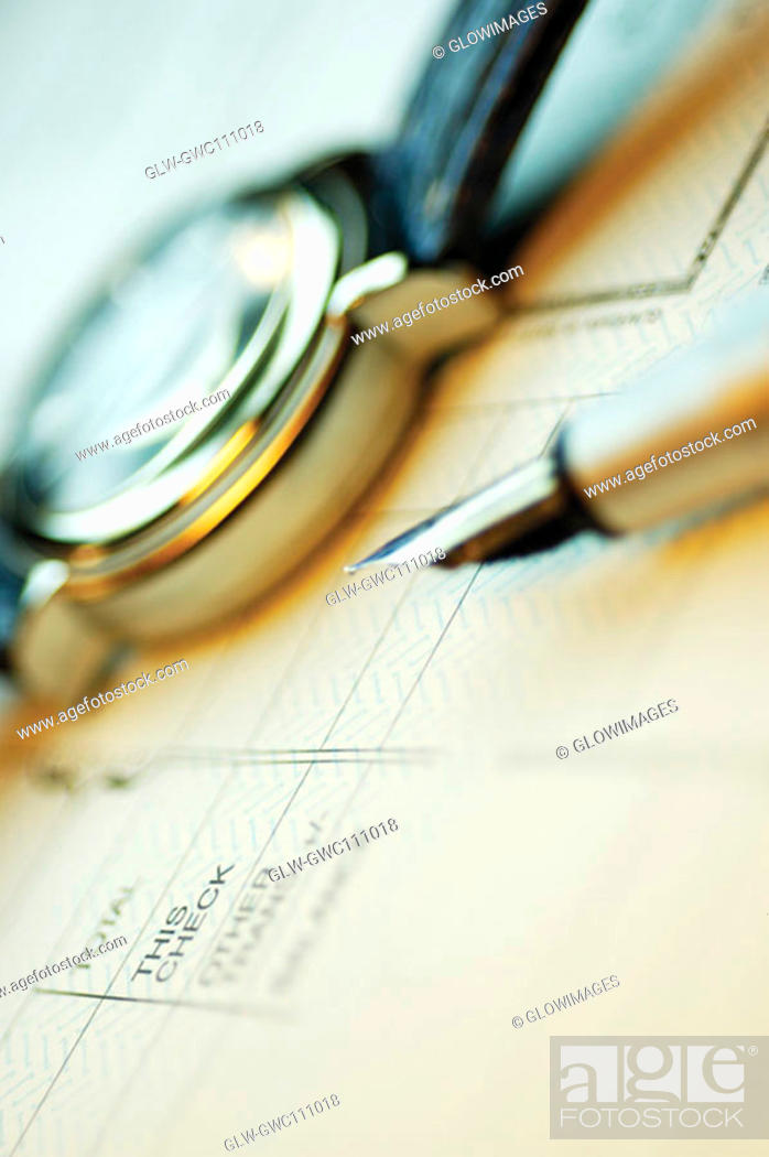Stock Photo: Close-up of a fountain pen and a wristwatch on a bank deposit slip.