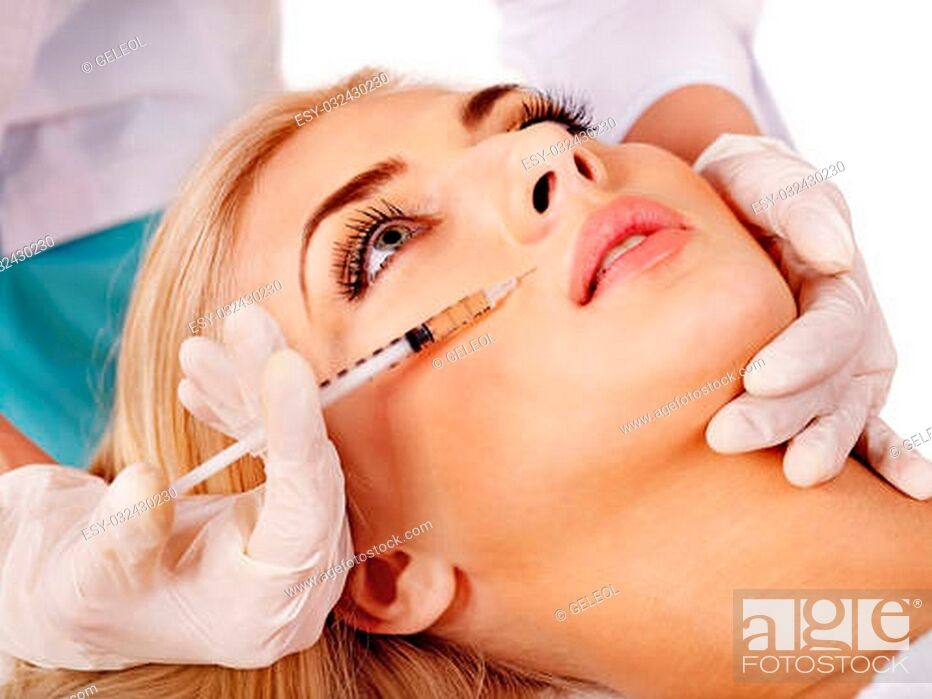 Imagen: Doctor woman giving botox injections. Isolated.