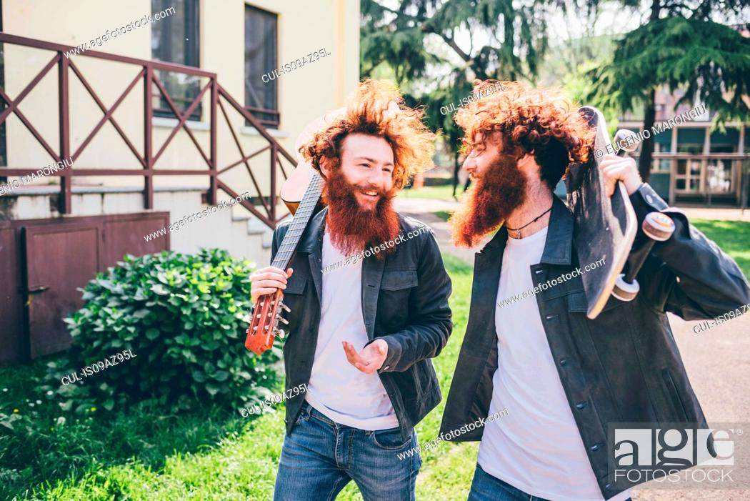 Imagen: Young male hipster skateboarder twins with red beards strolling in park.
