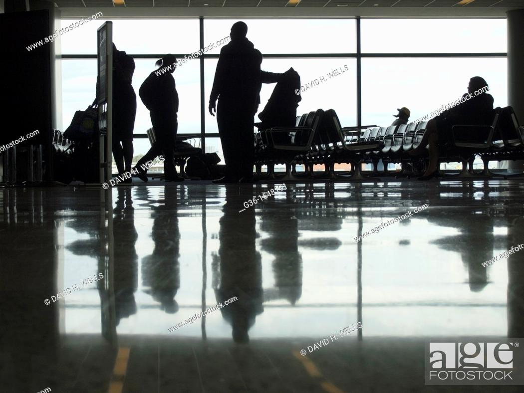 Stock Photo: Silhouettes of travelers in an airport terminal in Newark, New Jersey, United States.