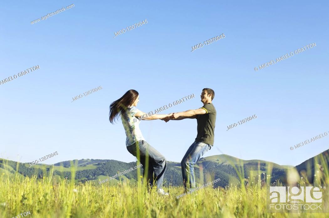 Stock Photo: Young couple dancing in mountain field side view ground view.