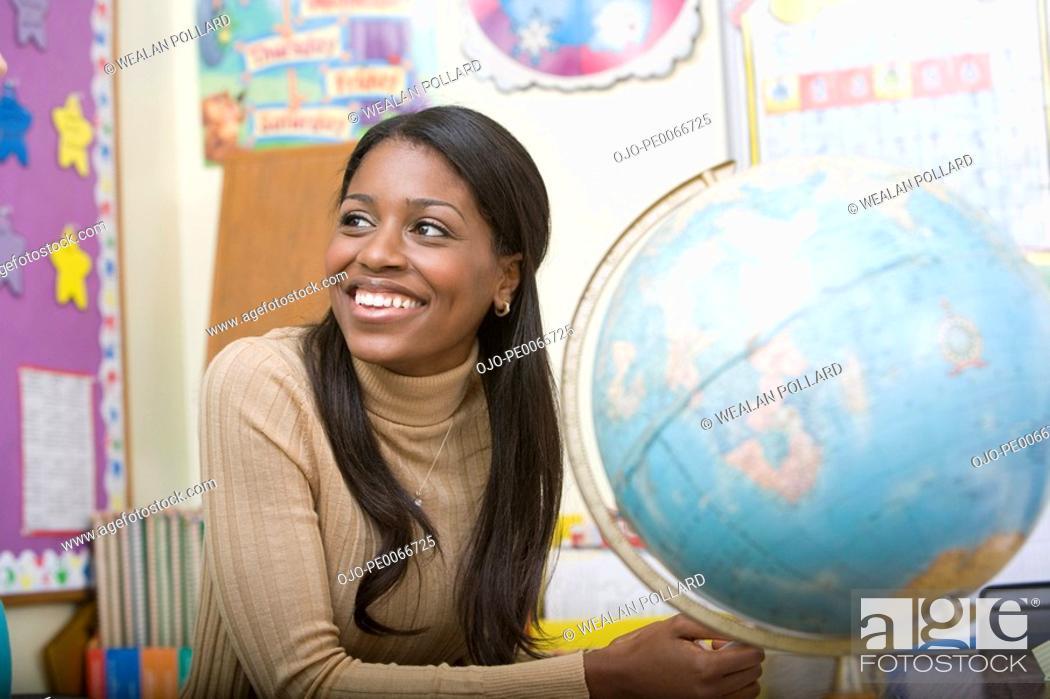 Stock Photo: Teacher at desk with globe.