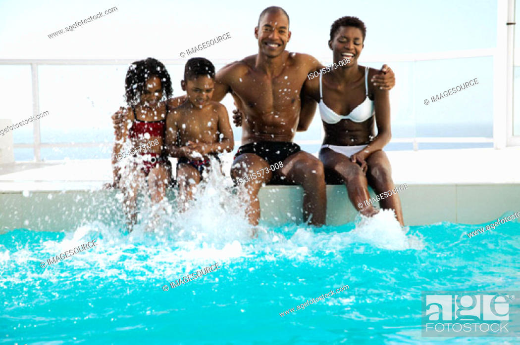 Stock Photo: Family sitting near pool.