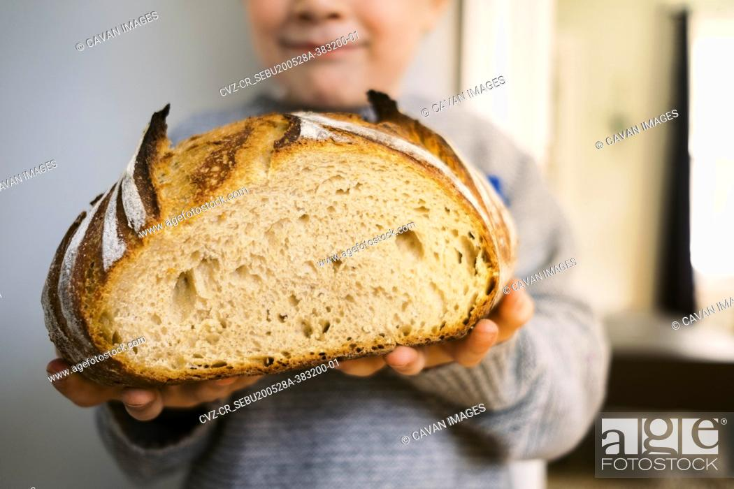 Stock Photo: Proud Preschooler showing off his homemade sourdough bread.