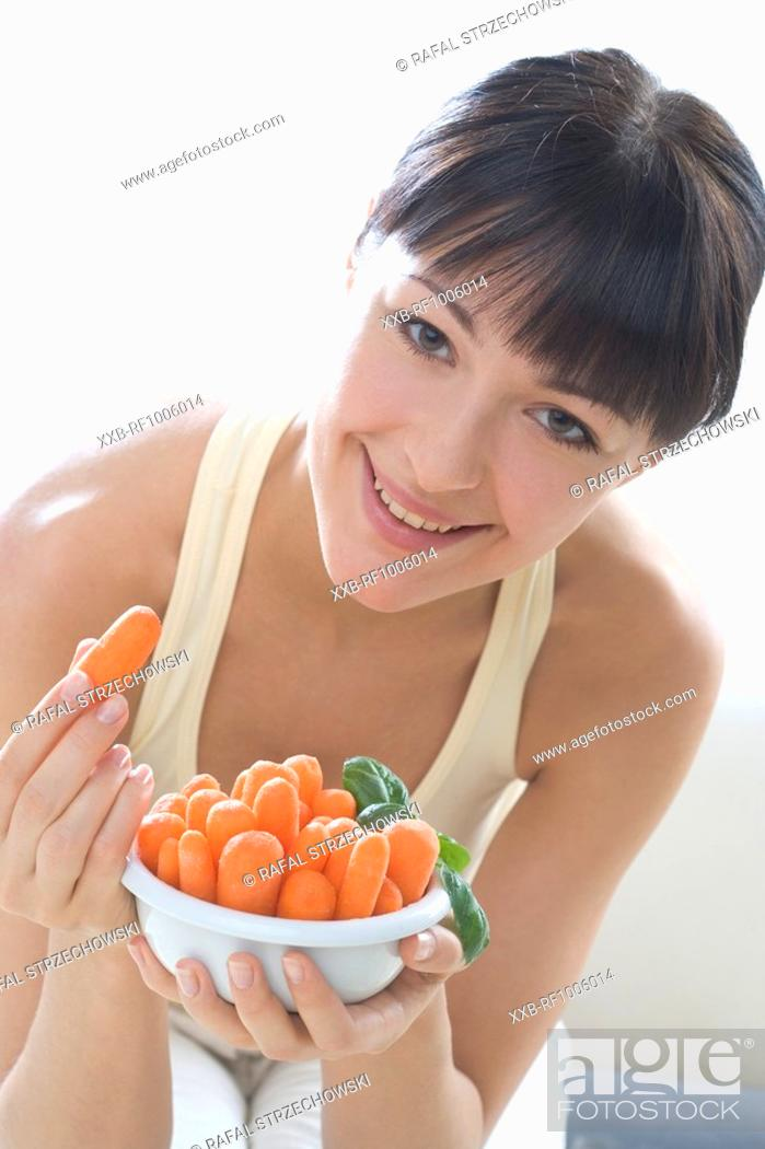 Stock Photo: woman with bowl of carrots.