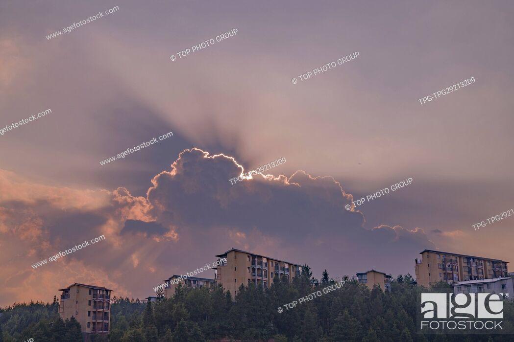 Stock Photo: sun behind cloud.