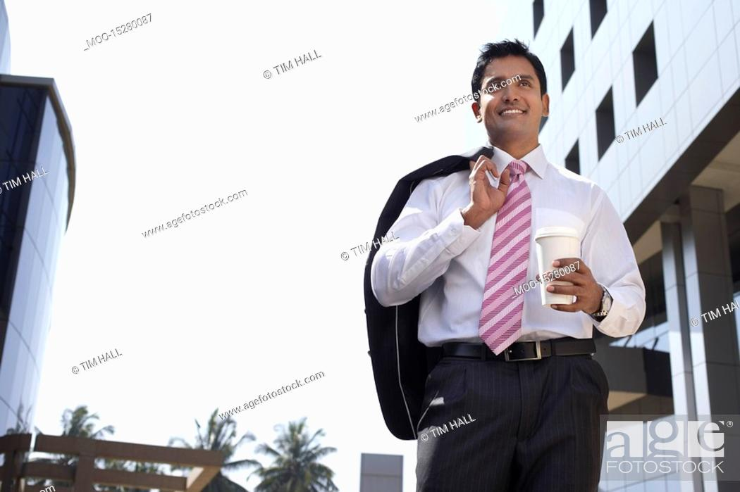 Stock Photo: Business man wearing hard hat on city rooftop.