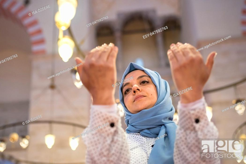 Stock Photo: Muslim woman in headscarf and hijab prays with her hands up in air with mosque on background. Religion praying concept.