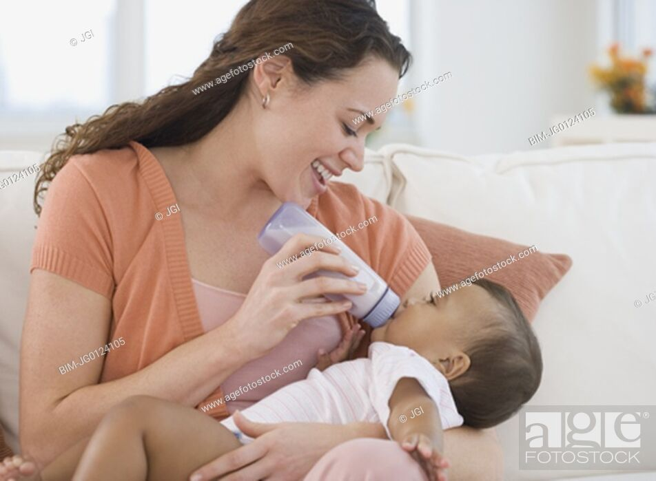 Stock Photo: Hispanic mother bottle feeding baby.