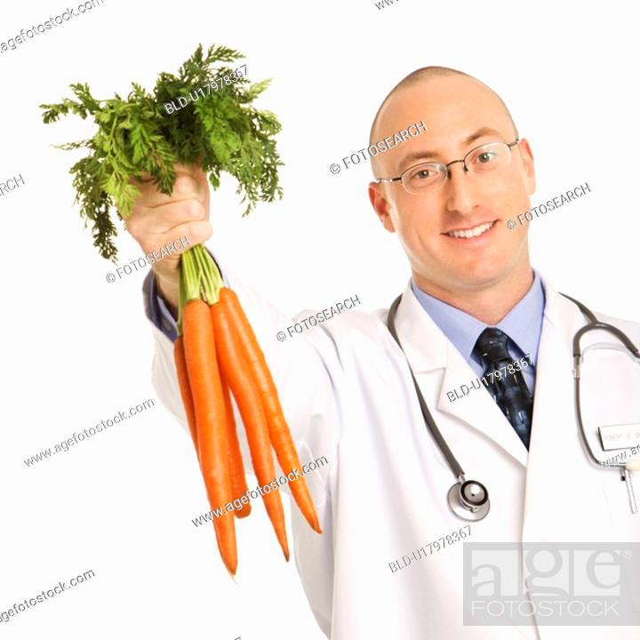 Stock Photo: Male physician holding bunch of carrots.
