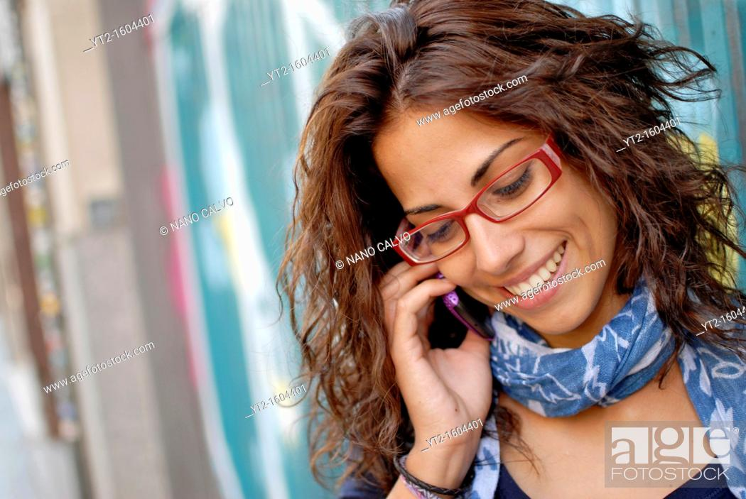 Stock Photo: Cute curly young woman talking on her mobile phone.