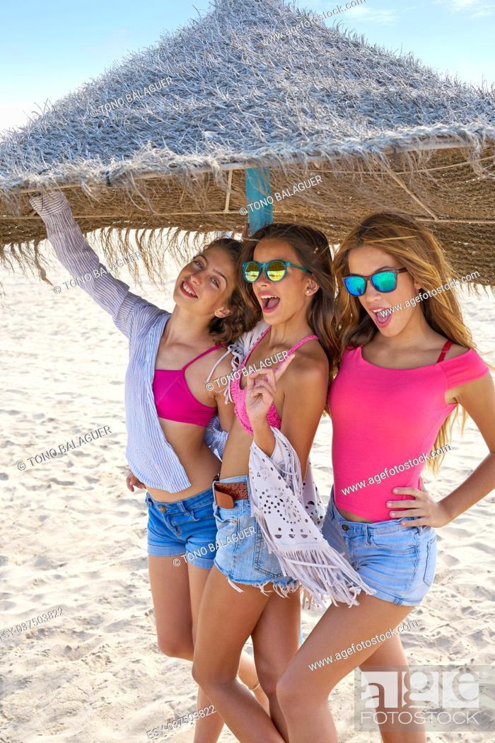 Stock Photo: teen best friends girls under thatch umbrella having fun on a beach.