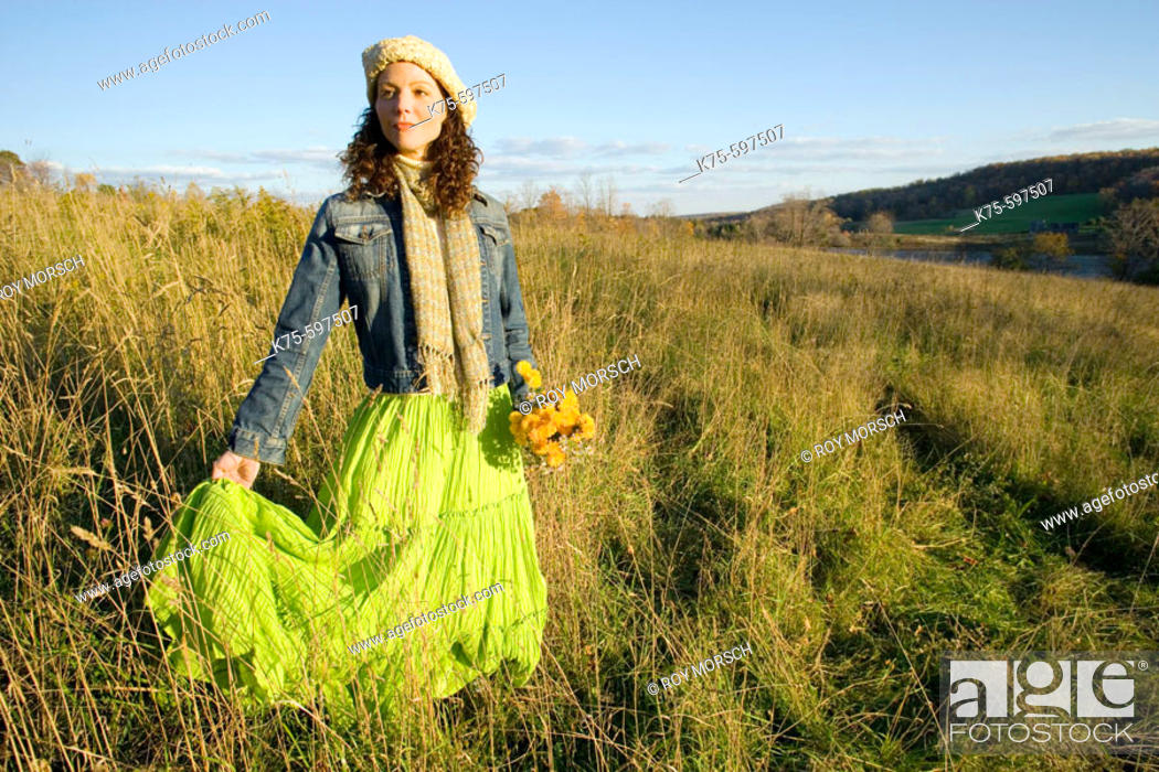 Stock Photo: Woman standing in field on hilltop.