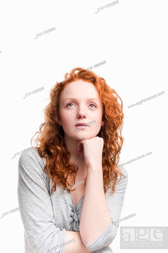 Stock Photo: Single red haired young woman in studio on white background.