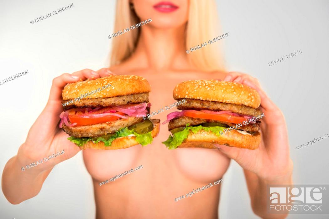 Stock Photo: Young naked woman keep in her hands two tasty burgers.