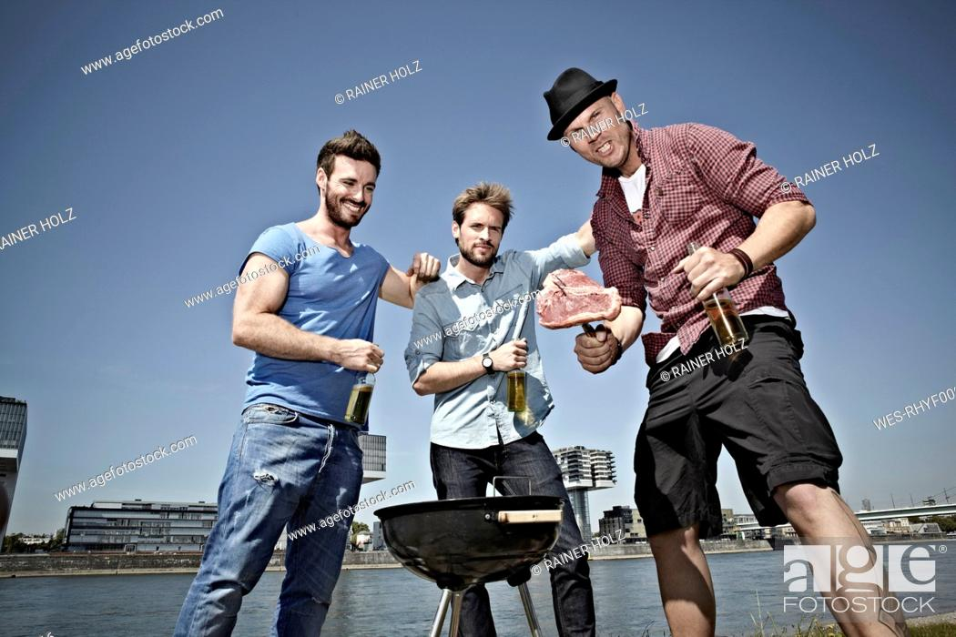 Stock Photo: Germany, Cologne, Young men gathered around barbecue and drinking beer.