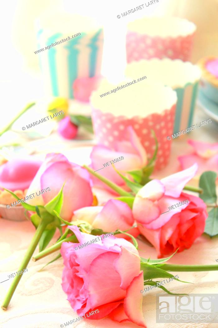 Stock Photo: Easter table with sweet eggs, pink roses and fresh cakes.