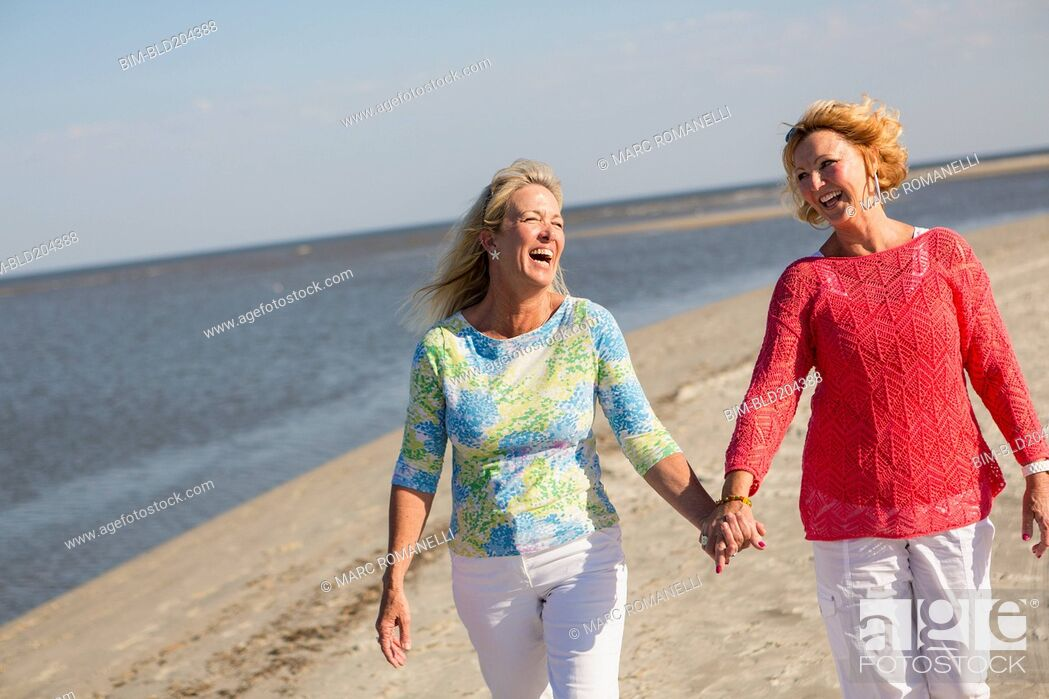 Stock Photo: Caucasian women walking on beach.
