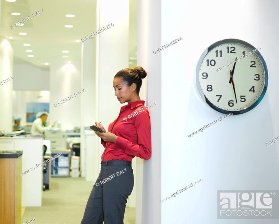 Stock Photo: Businesswoman in office using PDA near a clock.