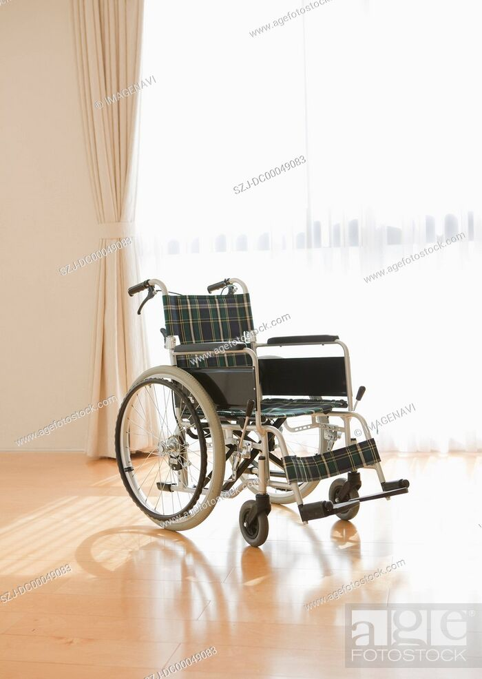 Stock Photo: Wheelchair by a window.