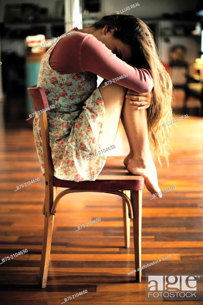 Stock Photo: Teenager girl with a country flowers dress seating with the legs on top of the chair and head in his arms thoughtfully fitness.