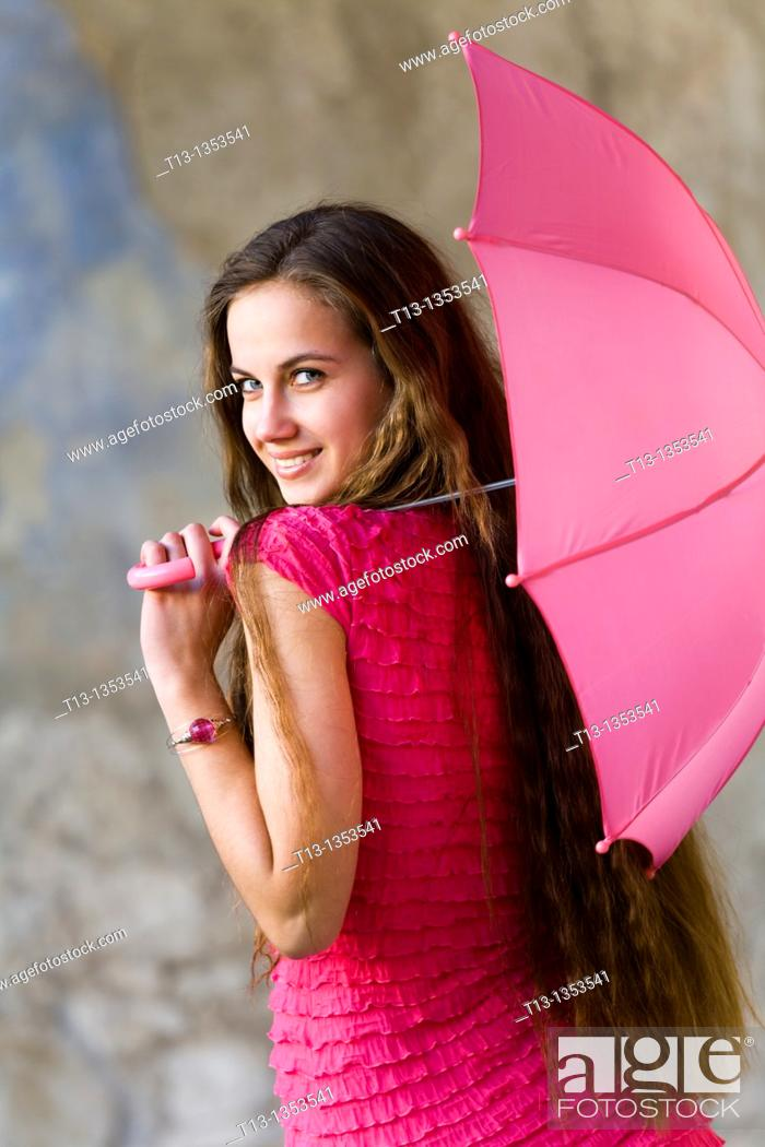Stock Photo: Flirting young woman with a small umbrella.