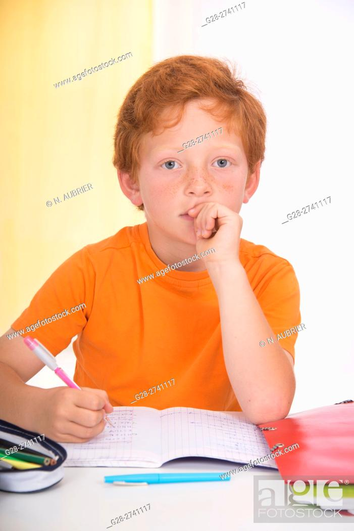 Stock Photo: Little boy doing his homework and looking thoughtful.