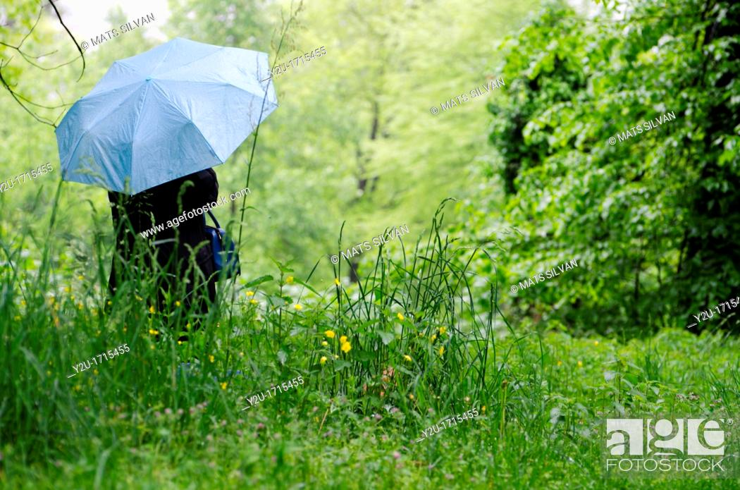 Stock Photo: Woman with a blue umbrella on the wet green field with grass and flowers.